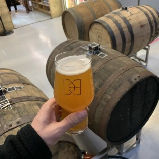 A pint of Double IPA and barrels of beer in Double Barrelled Taproom